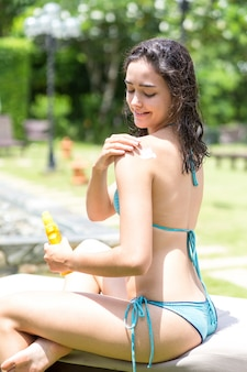 Bonne jeune femme appliquant un écran solaire sur l'épaule