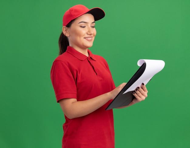 Bonne jeune femme de livraison en uniforme rouge et cap avec presse-papiers en le regardant avec le sourire sur le visage debout sur le mur vert