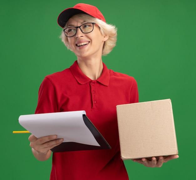 Bonne jeune femme de livraison en uniforme rouge et casquette portant des lunettes avec boîte en carton tenant le presse-papiers avec des pages blanches et un crayon à côté avec sourire sur le visage debout sur le mur vert