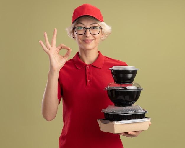 Bonne jeune femme de livraison en uniforme rouge et casquette portant des lunettes tenant pile de colis alimentaires souriant confiant montrant signe ok debout sur mur vert