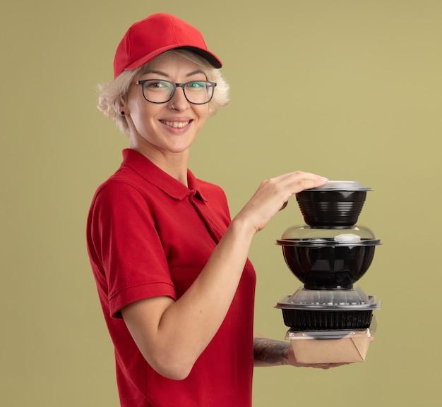 Bonne jeune femme de livraison en uniforme rouge et casquette portant des lunettes tenant pile de colis alimentaires souriant debout confiant sur mur vert