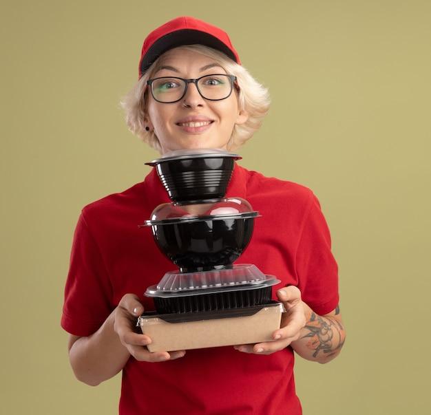 Bonne jeune femme de livraison en uniforme rouge et casquette portant des lunettes tenant pile de colis alimentaires souriant sympathique debout sur le mur vert