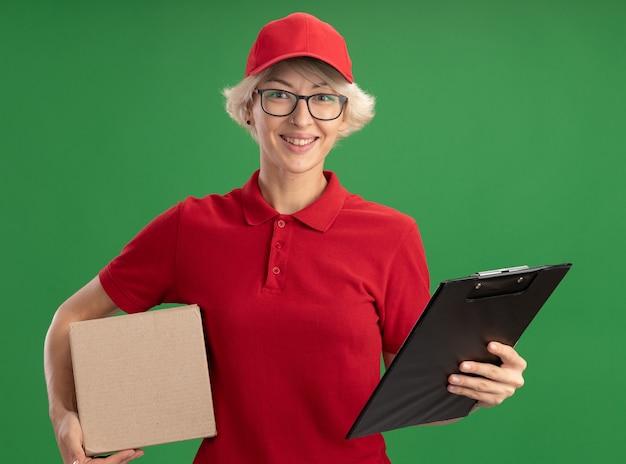 Bonne jeune femme de livraison en uniforme rouge et chapeau portant des lunettes avec presse-papiers de holdiong boîte en carton avec sourire sur le visage debout sur mur vert