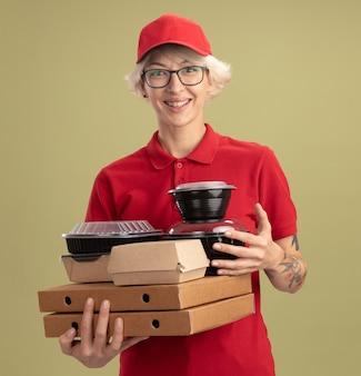 Bonne jeune femme de livraison en uniforme rouge et chapeau portant des lunettes tenant des boîtes de pizza et des emballages alimentaires souriant joyeusement debout sur le mur vert