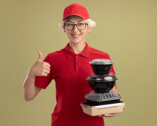 Bonne jeune femme de livraison en uniforme rouge et chapeau portant des lunettes tenant pile de colis alimentaires souriant confiant montrant les pouces vers le haut debout sur le mur vert