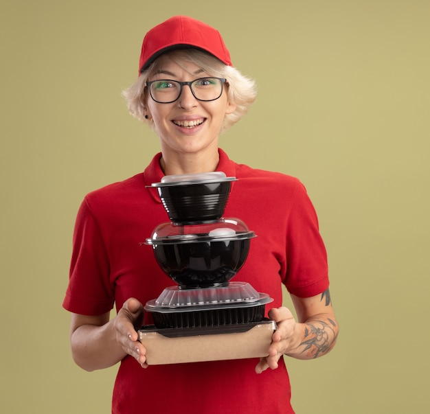 Bonne jeune femme de livraison en uniforme rouge et chapeau portant des lunettes tenant pile de paquets de nourriture souriant joyeusement debout sur le mur vert