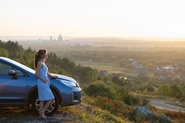 Bonne jeune femme pilote en robe bleue bénéficiant d'une chaude soirée d'été debout à côté de sa voiture. concept de voyage et de vacances.
