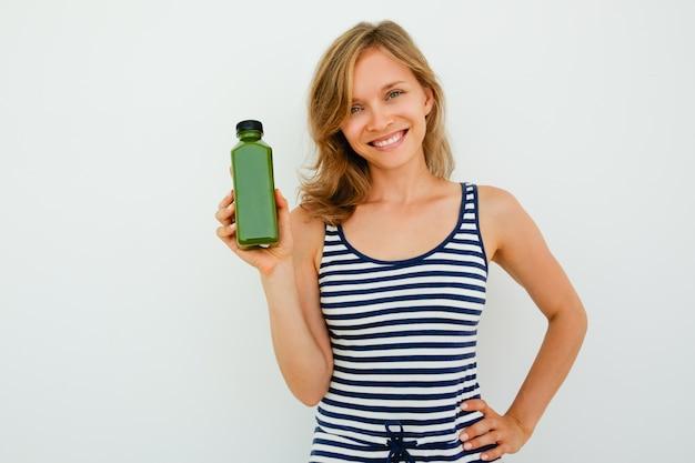 Bonne jeune femme qui recommande un bon shampooing et regarde la caméra en face du fond blanc. portrait de femme heureuse tenant la main sur la hanche et montrant un nouveau produit. concept de choix