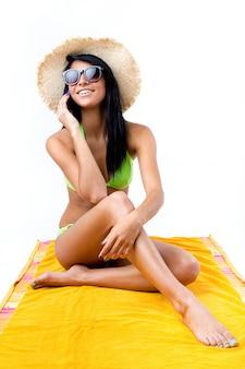 Bonne jeune fille au bikini vert parlant au téléphone mobile