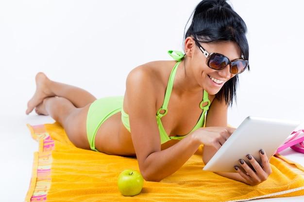 Bonne jeune fille au bikini vert et à la table numérique