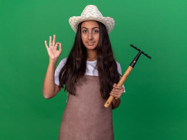 Bonne jeune fille de jardinier en tablier et chapeau d'été tenant mini râteau avec sourire sur le visage montrant signe ok debout sur le mur vert
