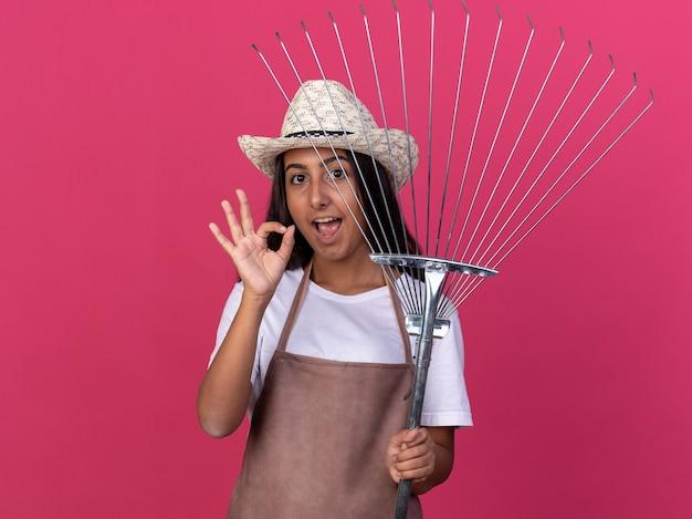 Bonne jeune fille de jardinier en tablier et chapeau d'été tenant le râteau avec le sourire sur le visage montrant signe ok debout sur le mur rose