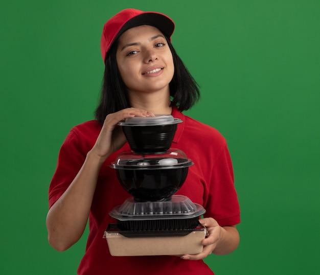 Bonne jeune fille de livraison en uniforme rouge et cap tenant la pile de colis alimentaires souriant sympathique debout sur le mur vert