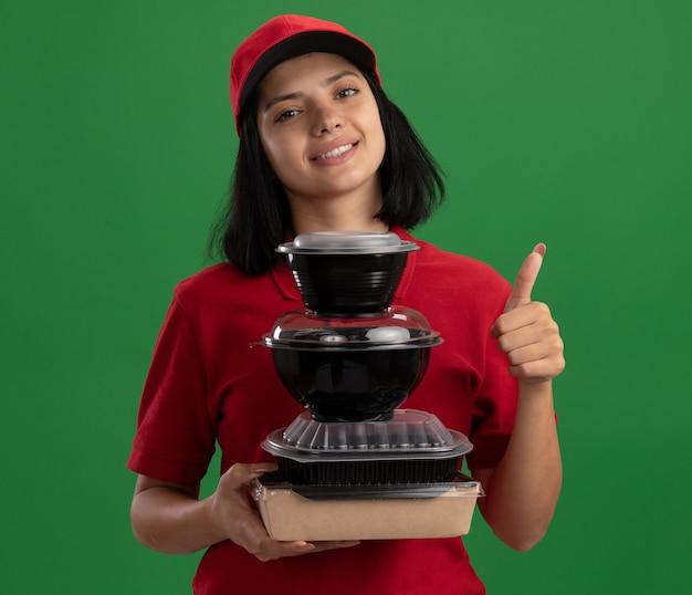 Bonne jeune fille de livraison en uniforme rouge et cap tenant la pile de paquets de nourriture souriant sympathique montrant les pouces vers le haut debout sur le mur vert
