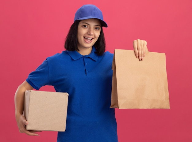 Bonne jeune livreuse en uniforme bleu et cap tenant le paquet de papier et boîte en carton souriant joyeusement debout sur le mur rose