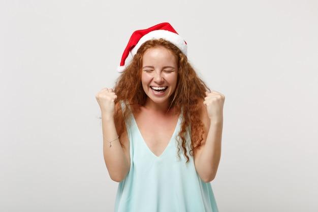Bonne jeune rousse santa girl en vêtements légers, chapeau de noël isolé sur fond blanc en studio. concept de vacances de célébration de bonne année 2020. maquette de l'espace de copie. serrer les poings comme un vainqueur.
