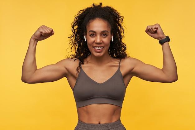 Bonne jeune sportive forte avec des écouteurs sans fil debout et montrant des muscles biceps isolés sur un mur jaune