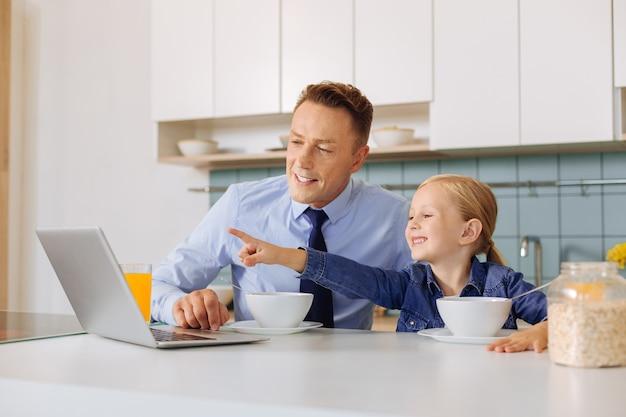 Bonne jolie jolie fille assise avec son père et pointant sur l'écran du portable