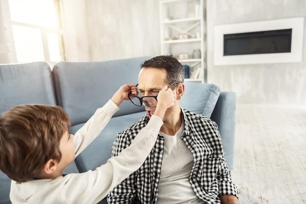 Bonne journée. bel homme aux cheveux noirs joyeux s'amusant avec son fils et le garçon mettant de grandes lunettes sur son papa alors qu'ils étaient assis sur le sol