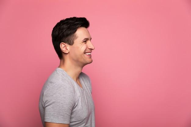 Bonne journée. bel homme, debout de profil et souriant.