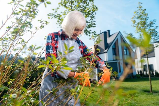 Bonne journée. belle vieille femme passant une journée tout en travaillant dans le jardin