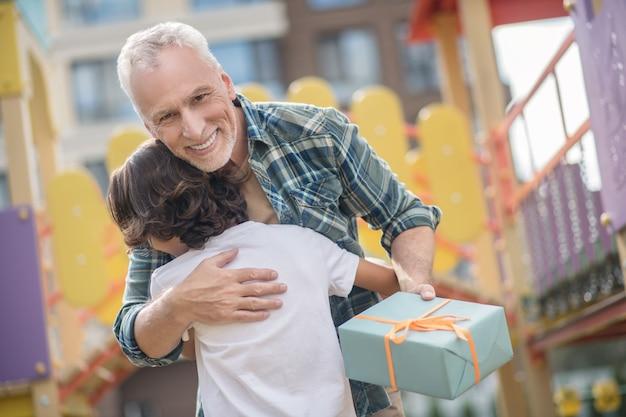 Bonne journée. heureux père donnant un cadeau à son fils et à la fois excité