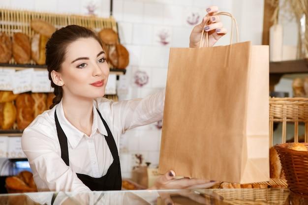 Bonne journée! portrait horizontal d'une magnifique femme boulanger passant sac en papier avec du pain au client