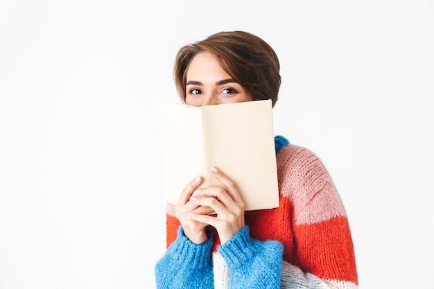Bonne joyeuse fille portant un pull assis sur une chaise isolée sur blanc, lisant un livre