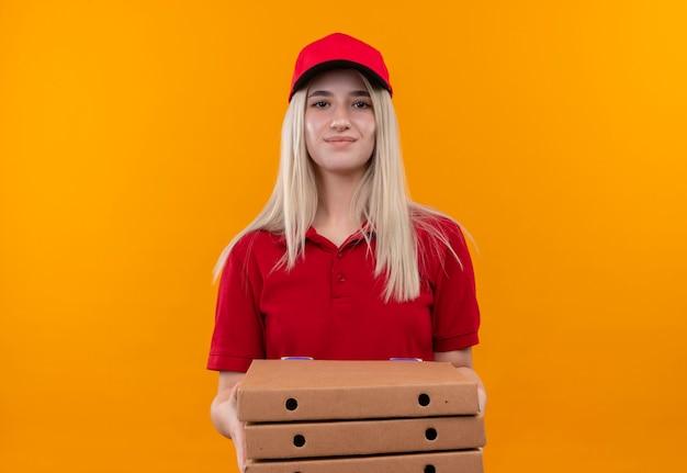 Bonne livraison jeune fille portant un t-shirt rouge et une casquette tenant une boîte à pizza sur fond orange isolé