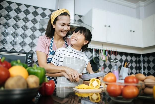 Bonne maman enseigne à sa fille la préparation et la découpe de légumes pour la cuisson.