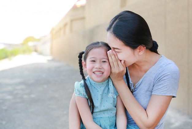 Bonne maman murmurant un secret à l'oreille de sa petite fille.