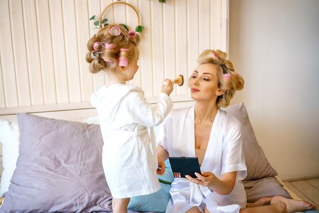 Bonne maman et sa fille font un maquillage assis sur le lit dans la chambre