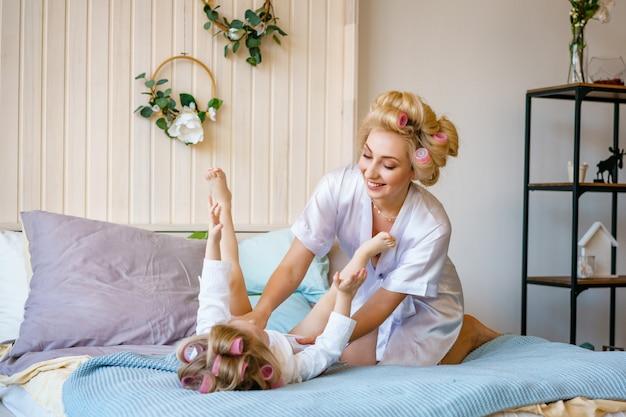 Bonne maman et sa fille s'amuser sur le lit en robe de chambre