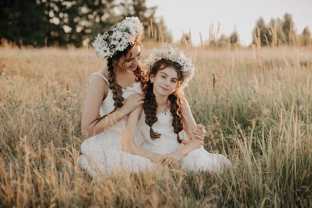 Bonne maman et sa fille en souriant et étreignant sur l'herbe dans le champ en été