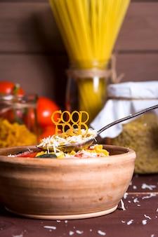 La bonne nourriture est garnie de pâtes sur une cuillère près d'une assiette