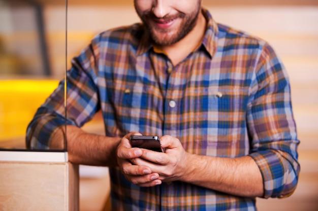 Bonne nouvelle d'un ami. beau jeune homme regardant son téléphone portable et souriant en se tenant debout à l'intérieur