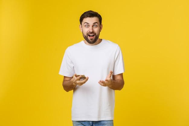 Bonne nouvelle d'un ami. confiant jeune bel homme en chemise jeans tenant un téléphone intelligent contre jaune