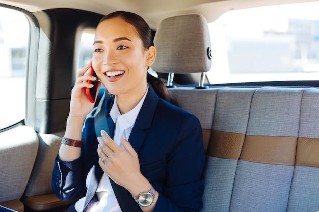 Bonne nouvelle. heureuse femme d'affaires joyeuse souriant tout en recevant d'agréables nouvelles