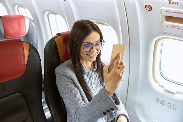Bonne passagère caucasienne dans le salon de l'avion avant de voler