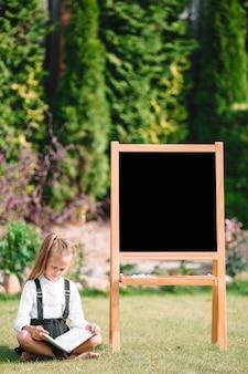 Bonne petite écolière avec un tableau en plein air