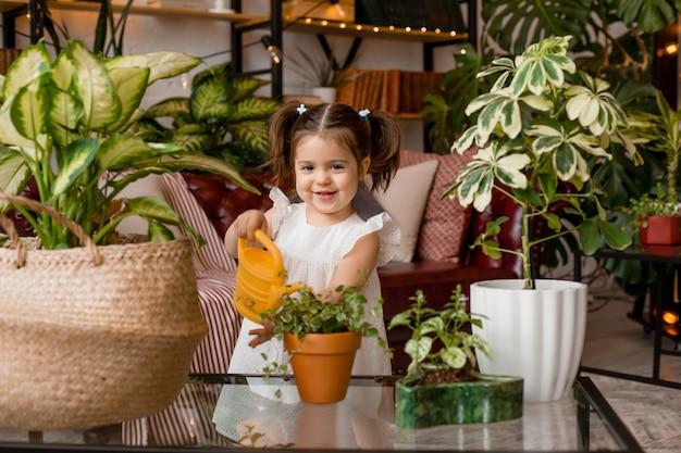Bonne petite fille avec un arrosoir arrose les fleurs dans la chambre