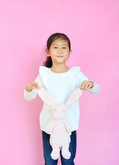 Bonne petite fille asiatique sur fond rose