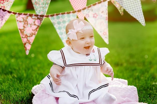 Bonne petite fille assise sur l'herbe avec des drapeaux