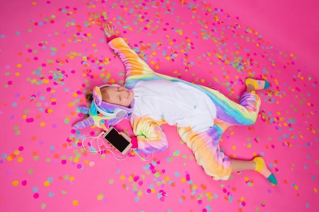Bonne petite fille blonde en licorne kigurumi écoute de la musique tenant dans la main smartphone sur une surface rose
