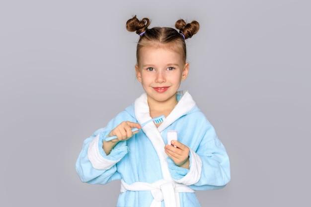 Bonne petite fille avec brosse à dents, dents et sourires