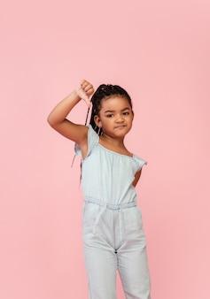 Bonne petite fille brune aux cheveux longs isolée sur fond rose avec copyspace