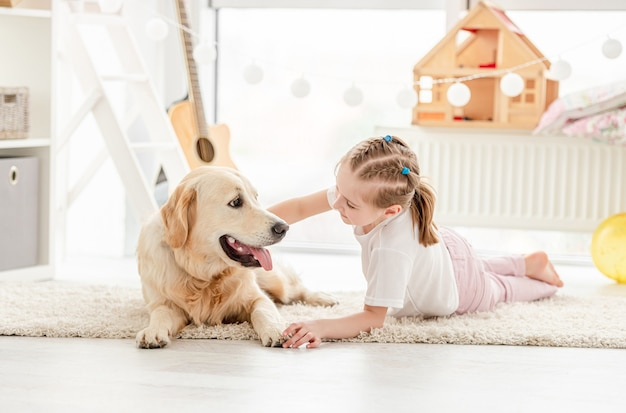 Bonne petite fille câlins beau chien dans la chambre des enfants