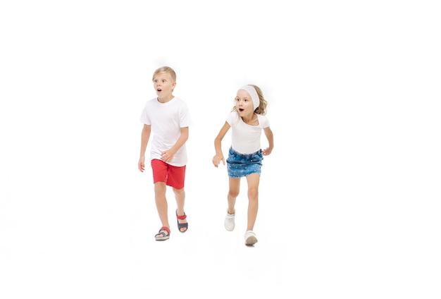 Bonne petite fille caucasienne et garçon sautant et courant isolé sur fond blanc