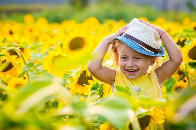 Bonne Petite Fille Sur Le Champ De Tournesols En été. Belle Petite Fille Aux Tournesols Photo Premium