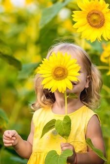 Bonne petite fille sur le champ de tournesols en été. belle petite fille aux tournesols